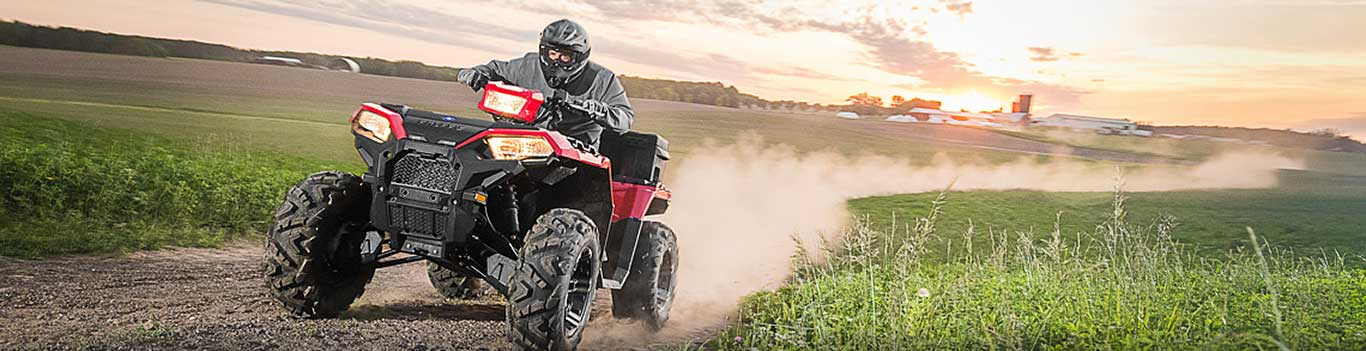 Man rides a red ATV across a dirt path near farm fields.